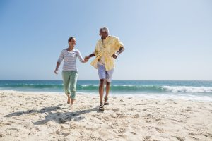 Happy senior couple running on the beach. iStockalypse LA California