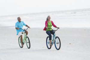 A happy, mature couple riding their bicycles on the sand at the beach, with water and sky in the background.  The woman is in front and her husband is following behind her.