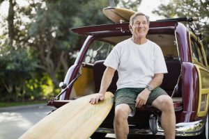 Smiling senior man with surfboard sitting on tailgate of vintage car