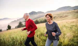 Senior couple running outdoors in nature in the foggy morning.